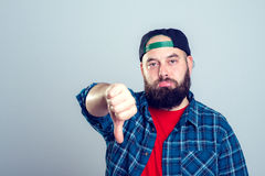 Bearded man with baseball cap with thumb down Stock Photography