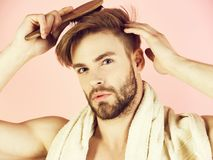 Bearded man with bathing towel on neck combing healthy hair. Bearded man or handsome macho with bathing towel on neck combing healthy blond hair with brush in stock photo