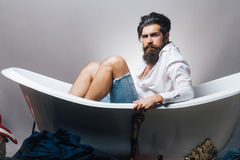 Bearded man in bathtub. Young handsome bearded man with long beard sitting in bathtub on grey studio background Stock Image