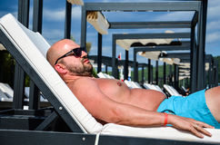 Bearded man at the beach. Handsome tanned bearded muscular man relaxing  on the beach Royalty Free Stock Image