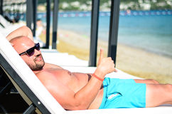 Bearded man at the beach. Handsome tanned bearded muscular man relaxing  on the beach Stock Photo