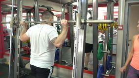 A bearded man with a beard performs an exercise in the gym, squatting with a barbell under the supervision of a