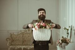 Bearded man. Bearded man hold basket with flowers. Bearded man with beard on happy face. Bearded man smile with floral royalty free stock photo