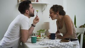 Bearded man and beautiful woman are eating dinner and kissing at table in home kitchen spbd.