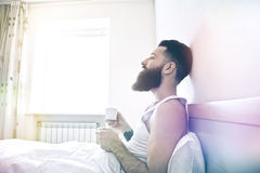 Man in bed drinking morning coffee stock image