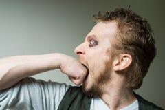 Bearded man biting his fist. Stock Image