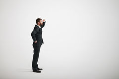 A bearded man in a black business suit looks into the distance Stock Images