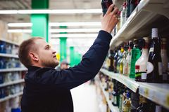 Bearded man, In a black jacket, stopped to make my choice in store window, holds a bottle of strong alcohol. In his hand, taking from shelf Royalty Free Stock Images