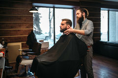 Bearded man in black salon cape visit barbershop. Bearded customer men in black salon cape visit barbershop. Coiffeur at work royalty free stock photography