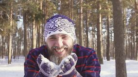 Bearded man blows snow from palm and smiles. Bearded man blowing snow from palm and smiling looking at camera, winter forest stock video