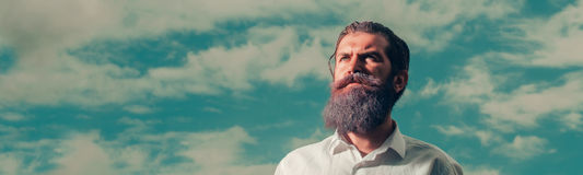 Bearded man with blue beard on sky. Young handsome bearded man with long beard blue color and serious face in white shirt sunny day outdoor on natural cloudy sky Royalty Free Stock Photography