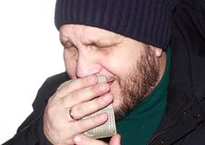 A bearded man in a blue down jacket and a knitted hat coughs, covering his mouth with a handkerchief. A simple bearded man with a sore throat in a blue down Stock Photo