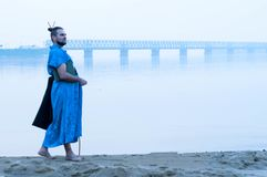 Bearded man in blue kimono with book on river bank stock photo