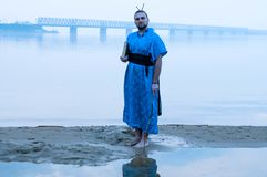 Bearded man in blue kimono holding book on river bank in fog and looking at camera stock image