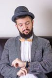 Bearded man with a bow tie. Bearded man in a suit wearing a bow tie cheking time stock photos