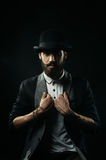The bearded man in a bowler hat holding his lapels Stock Photos