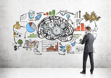 Bearded man, brain and gears on concrete. Rear view of a bearded businessman looking at a brain sketch with gears and a startup drawing on a concrete wall Stock Photo