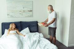 Bearded man bringing tray with breakfast to happy blonde woman in bedroom Royalty Free Stock Image