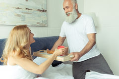 Bearded man bringing tray with breakfast to happy blonde woman in bedroom Stock Image