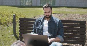 Browsing the Internet. Bearded man browsing the internet sitting on the bench outdoor stock video
