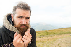 Bearded man, brutal caucasian hipster with moustache cold on mountain. Bearded man, long beard, brutal caucasian hipster with moustache on serious face, unshaven stock photography