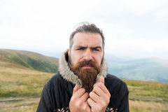 Bearded man, brutal caucasian hipster with moustache cold on mountain. Bearded man, long beard, brutal caucasian hipster with moustache on serious face, unshaven royalty free stock images