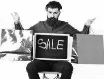 Bearded man, brutal caucasian hipster with moustache holding shopping packages. Bearded man, long beard. Brutal caucasian serious hipster with moustache holding royalty free stock photo