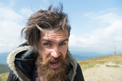 Bearded man, brutal caucasian hipster with moustache on windy mountain. Bearded man, long beard, brutal caucasian hipster with moustache on surprised face royalty free stock photography