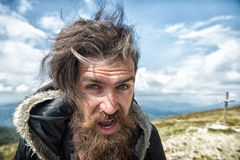 Bearded man, brutal caucasian hipster with moustache on windy mountain. Bearded man, long beard, brutal caucasian hipster with moustache on surprised face stock photo