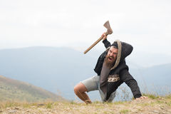 Bearded man, brutal hipster with moustache holds axe on mountain. Bearded man, long beard, brutal caucasian hipster with moustache holds axe with angry face on royalty free stock photography