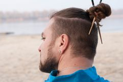 Bearded man with bun and sticks on head in blue kimono looking away stock image