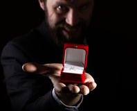 Bearded man in business suit gives a ring in the red box and expresses different emotions on dark background Royalty Free Stock Image