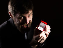 Bearded man in business suit gives a ring in the red box and expresses different emotions on dark background Royalty Free Stock Photos