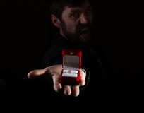 Bearded man in business suit gives a ring in the red box and expresses different emotions on dark background Royalty Free Stock Photo