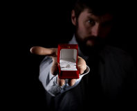 Bearded man in business suit gives a ring in the red box and expresses different emotions on dark background Stock Images