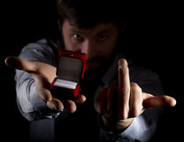 Bearded man in business suit gives a ring in the red box and showing middle finger on dark background Stock Images