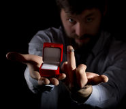 Bearded man in business suit gives a ring in the red box and showing middle finger on dark background Royalty Free Stock Photo