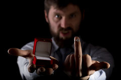 Bearded man in business suit gives a ring in the red box and showing middle finger on dark background Stock Photos