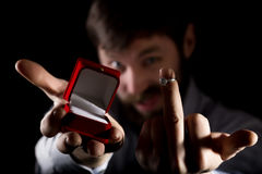 Bearded man in business suit gives a ring in the red box and showing middle finger on dark background Royalty Free Stock Photos