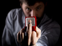 Bearded man in business suit gives a ring in the red box and showing middle finger on dark background Royalty Free Stock Image