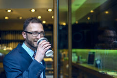 Bearded man in business suit sipping coffee Stock Photo