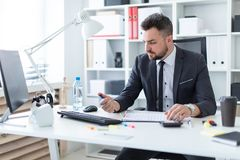 A man sits at the office at the table and clicks a pen. A bearded man with a business suit is working in a bright office. photo with depth of field Stock Photo