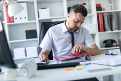 A man sits at a table in the office and looks at the wristwatch. A bearded man with a business suit is working in a bright office. photo with depth of field Stock Images