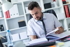 A man is sitting in the office and scrolls through the documents. A bearded man with a business suit is working in a bright office. photo with depth of field Royalty Free Stock Photo