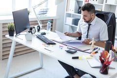 A man is sitting in the office and scrolls through the documents. A bearded man with a business suit is working in a bright office. photo with depth of field Royalty Free Stock Photography