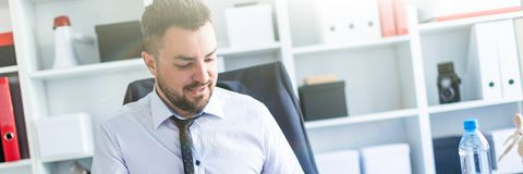 A man is sitting in the office and working with documents. A bearded man with a business suit is working in a bright office. photo with depth of field stock photography