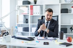 A man is sitting in a chair in the office at the table. A bearded man with a business suit is working in a bright office. photo with depth of field Royalty Free Stock Photo
