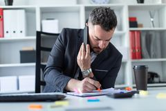 A man is sitting at the desk at the office, talking on the phone and writing a marker in the document. A bearded man with a business suit is working in a bright Stock Images