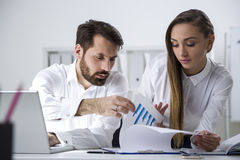 Bearded man, businesswoman and a graph Stock Photos