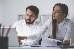 Bearded man and businesswoman in office Stock Images